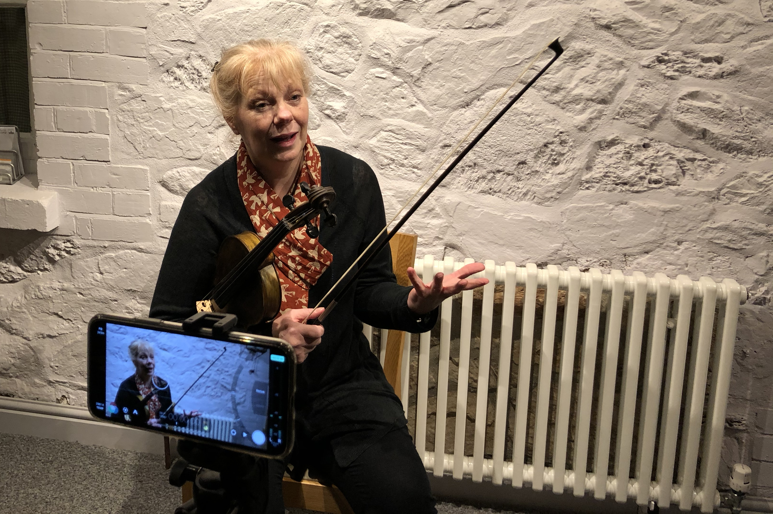 Gillian Taylor with a violin under her arm, being filmed on a mobile phone