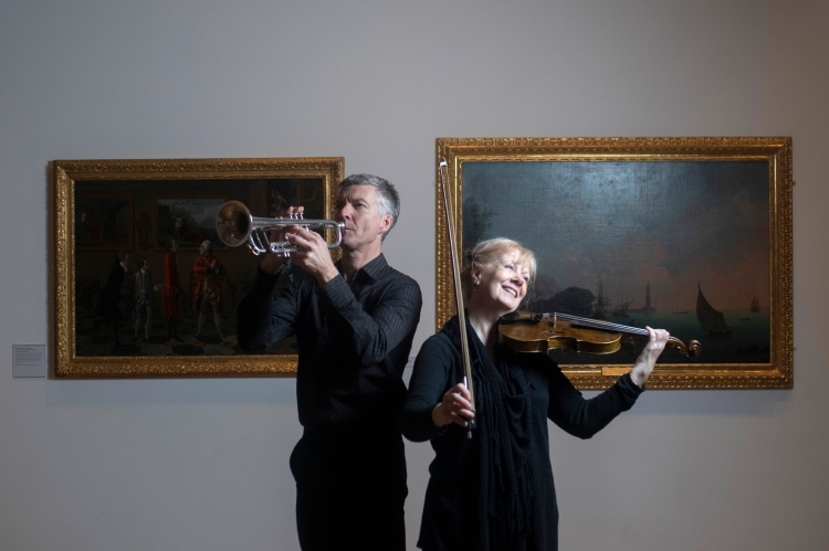 Man playing trumpet, alongside Gillian Taylor playing violin in an art gallery