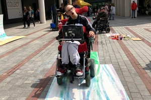 Man creating art using the wheels of his wheelchair and paint