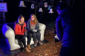 TV interviewer with microphone interviewing someone on a sofa outdoors, with decorative lighting. Camera operator filming.