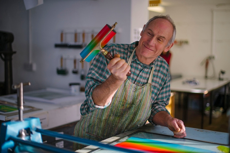 Man in print studio holding print roller with colourful inks