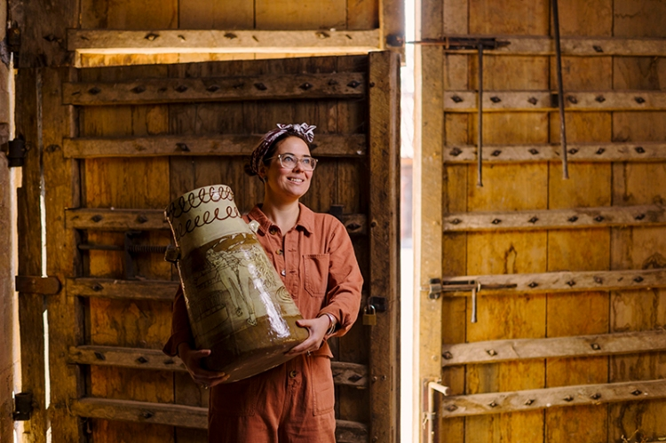 Woman standing in front of huge barn door, holding a large ceramic pot
