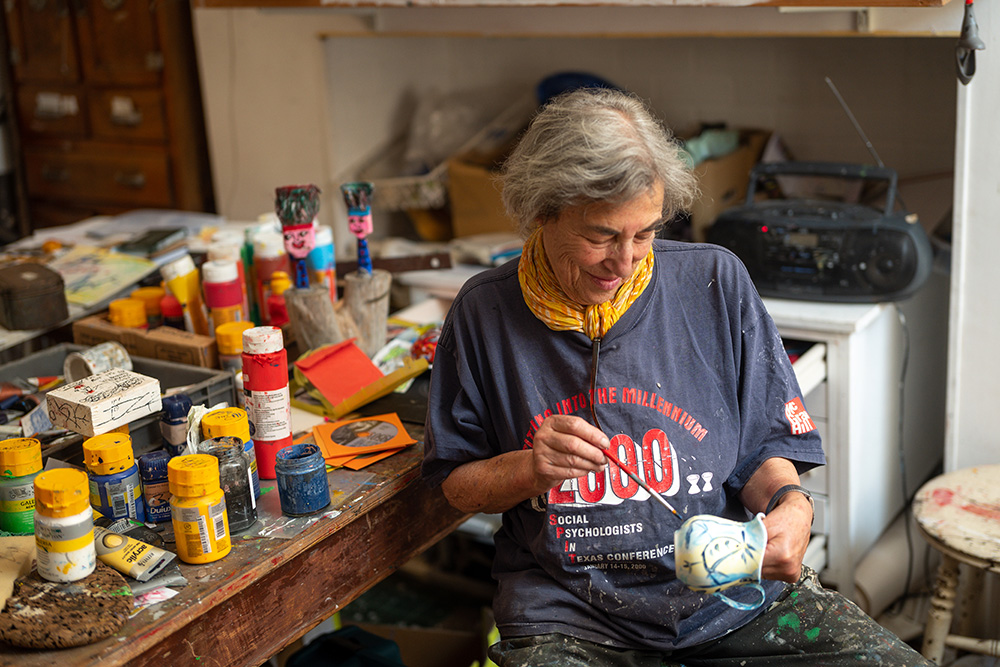 Artist painting onto a ceramic jug in her studio, surrounded by paints