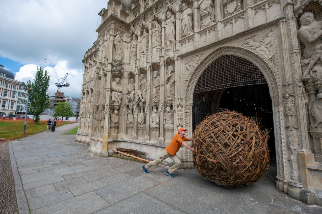 Man with orange top pushing a huge woven willow ball through the doors of the cathedral