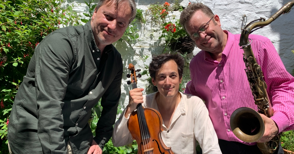 Composer Tom Vignieri, Viola player David Yang, and Sax player Andy Williamson. David holding a viola, Andy holding a sax. They're in a garden.